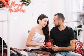 Man and woman sitting on bed
