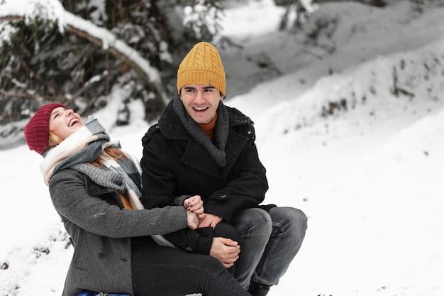 Мужчина и женщина сидят на санях и смеются