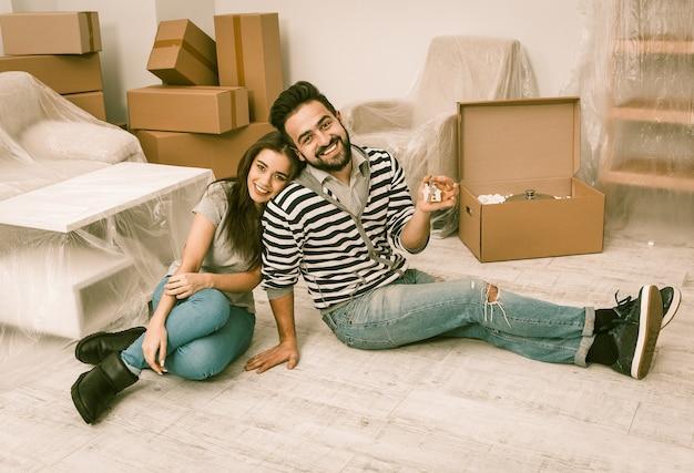 Мужчина и женщина, улыбаясь, готовятся к переезду в новый дом.