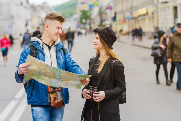 Мужчина и женщина, улыбаясь с картой Бесплатные Фотографии
