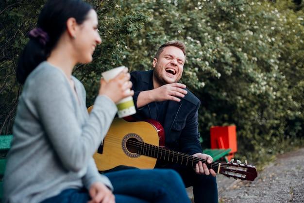 야외에서 기타와 함께 시간을 보내는 남자와 여자