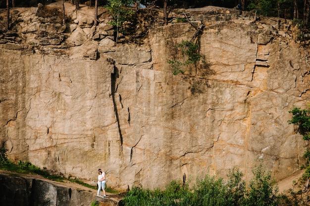 男と女が立って岩の表面を抱きしめます