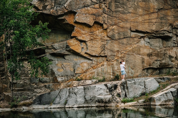 男と女が立って、岩の表面で手に抱きしめます
