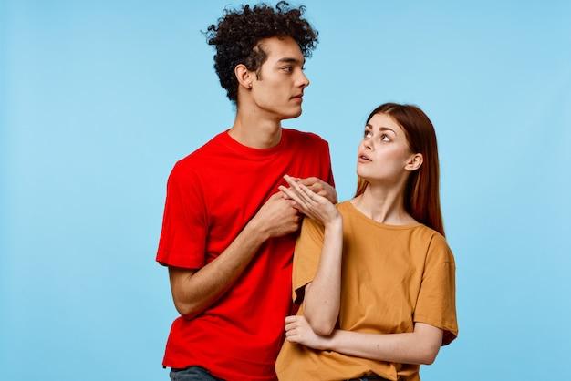 男性と女性が並んで立っているコミュニケーションファッションモダンなスタイルの青い背景