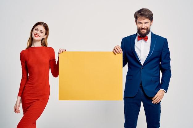 男性と女性が並んで立っている黄色のモックアップ広告ライト背景コピースペース