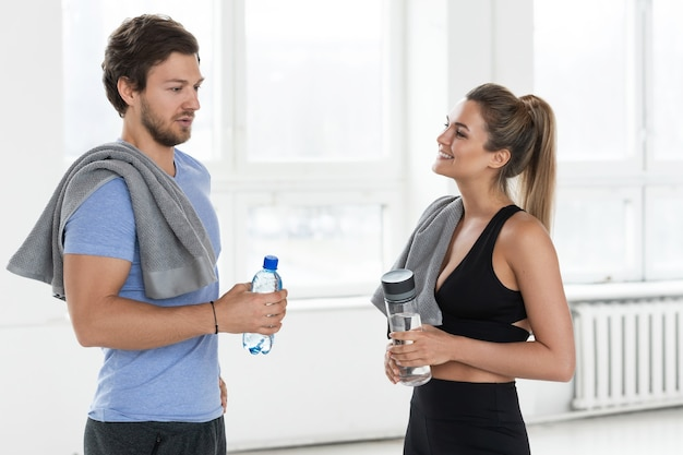Мужчина и женщина разговаривают после хорошей тренировки в тренажерном зале. пара, держащая бутылки с водой и полотенца обсуждает тренировочный процесс.