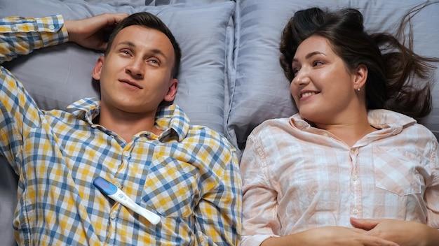 妊娠検査、上面図を議論しているベッドに横たわっている間話している男性と女性。