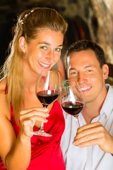 지하실에 남자와 여자 태스킹 와인