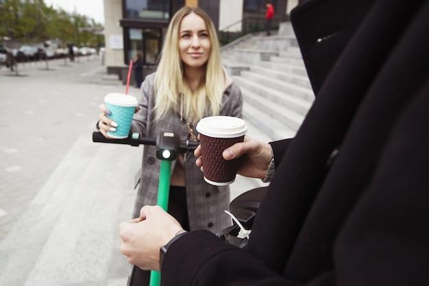 男と女は、おいしいカプチーノを求めて街を走り回る電動スクーターから休憩しました。