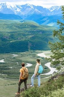 배낭을 메고 있는 남녀 관광객들은 여행 중에 아름다운 산을 바라보고 있습니다. 여행 컨셉