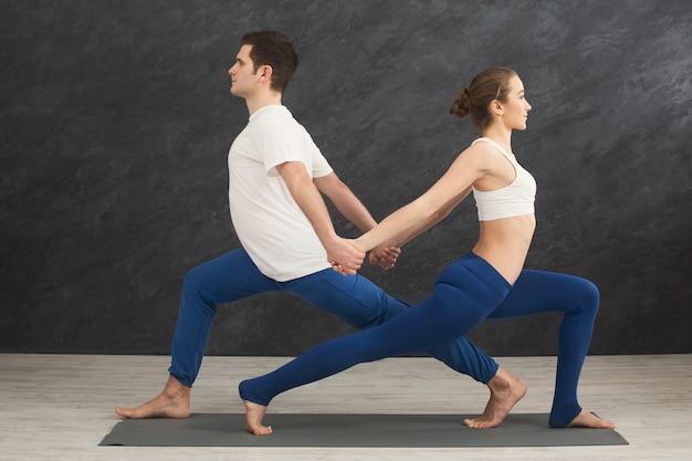 バランスの取れたポーズでヨガをトレーニングする男性と女性。若いカップルがリラックスした運動をし、背中合わせに立って、スペースをコピーします。パートナーヨガ、信頼の概念