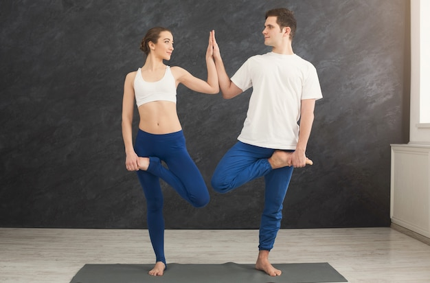 バランスの取れたポーズでヨガをトレーニングする男性と女性。若いカップルがリラックスした運動をし、一緒に立って、スペースをコピーします。パートナーヨガのコンセプト