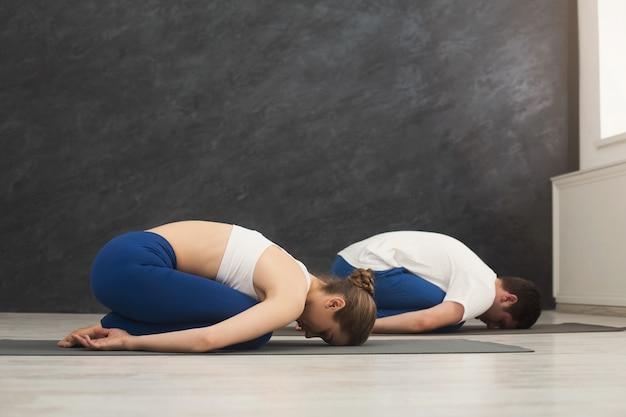남자와 여자는 아이의 포즈로 요가를 훈련하고 공간을 복사합니다. 스포티 한 젊은 부부는 체육관에서 매트에서 함께 에어로빅 운동을 합니다.