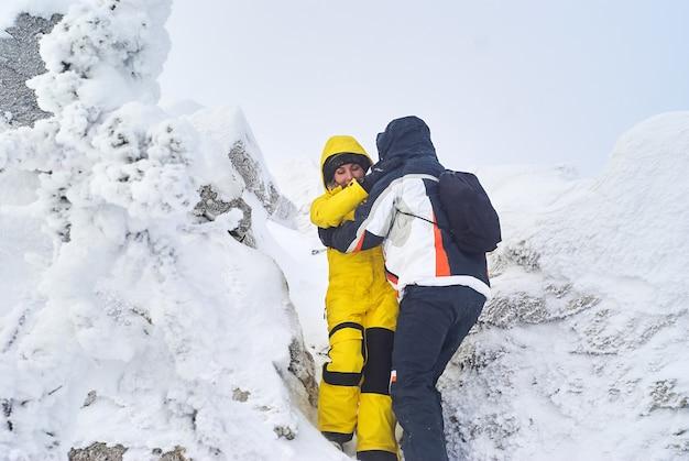 남자와 여자 여행자는 서로 도우며 눈 덮인 산 정상에서 내려온다