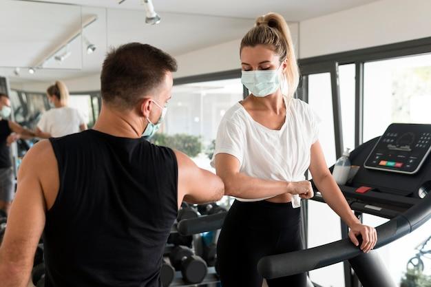 남자와 여자는 팔꿈치를 사용하여 체육관에서 서로 경례