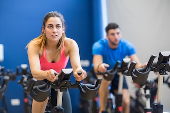 Man and woman using exercise bikes