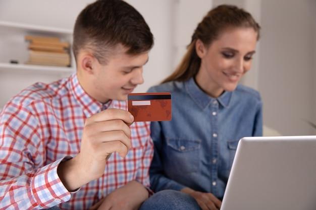 家に座ってオンラインショッピングをするインターネットを使用する男性と女性。