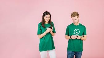 Man and woman using mobile phone on pink background