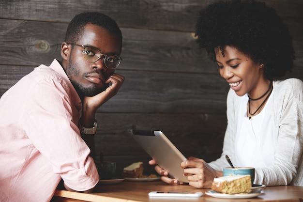 男と女のカフェでタブレットを使用して