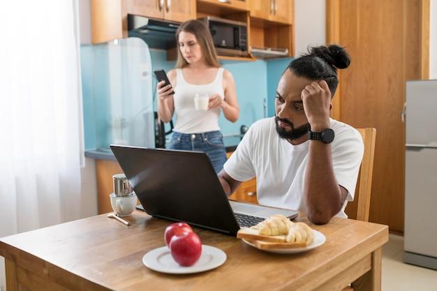 Мужчина и женщина, использующие свой телефон на кухне