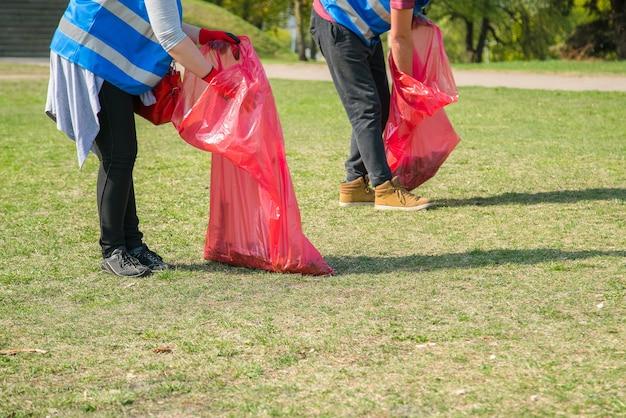 Мужчина и женщина добровольно собирают мусор и пластиковые отходы в общественном парке. молодые люди в перчатках кладут мусор в красные полиэтиленовые пакеты на открытом воздухе