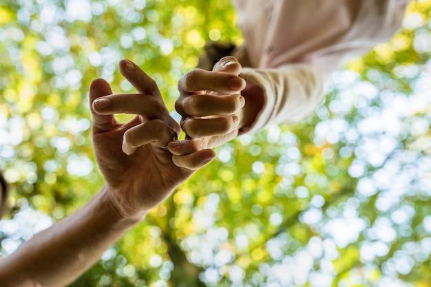 愛情と愛のしるしでリンクされた指と一緒に歩いている男性と女性。