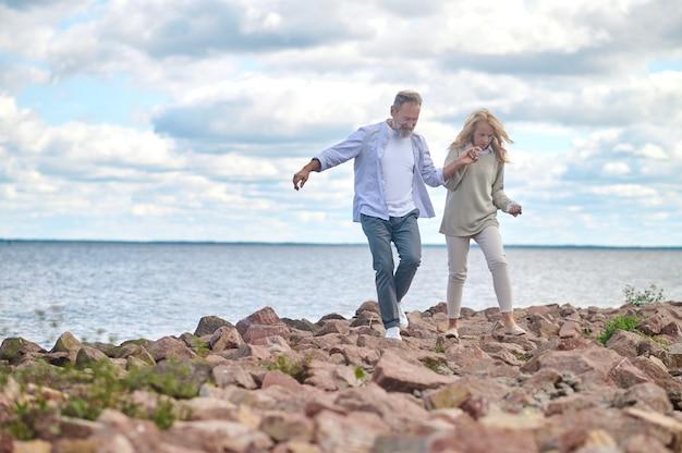 海の近くで手で歩く男女