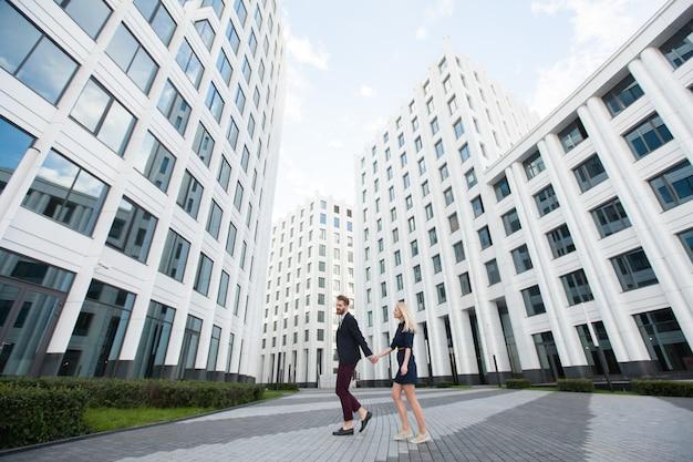 Мужчина и женщина, идущая рука на фоне здания бизнес-центра.