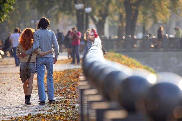 ウォーターフロントに沿って一緒に歩いている男性と女性。愛と新しい家族。