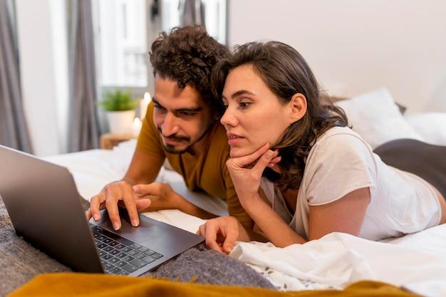 Мужчина и женщина смотрят фильм на своем ноутбуке
