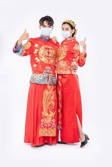남자와 여자는 치파오 정장과 마스크를 착용 중국 새해에 이벤트에 엄지 손가락을 올립니다