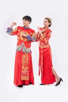 남자와 여자는 중국 새해에 이벤트가 발생할 것을 기뻐하는 cheongsam 정장을 입는다.