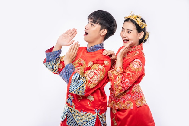 男性と女性がチャイナドレスを着て中国の旧正月に驚くべきプロモーションイベントを叫ぶ