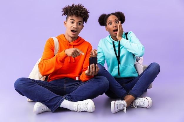 Мужчина и женщина в рюкзаках, используя мобильный телефон, сидя на полу со скрещенными ногами, изолированными над фиолетовой стеной