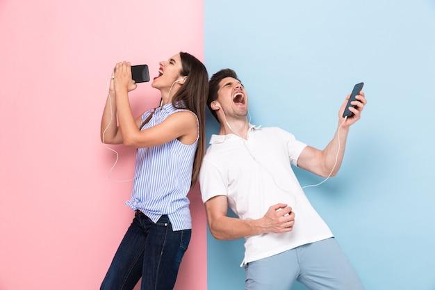 Мужчина и женщина в наушниках поют во время прослушивания музыки на смартфонах, изолированных на красочной стене