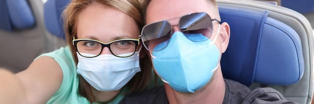 飛行機で医療用保護マスクを着用している男性と女性