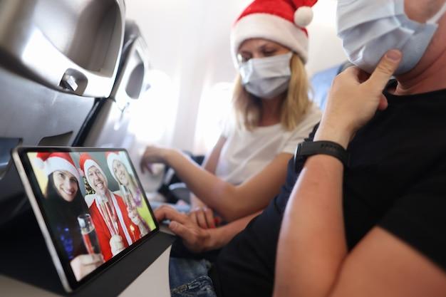 Мужчина и женщина в защитных масках и шляпах санта-клауса летят в самолете и проводят конференцию ...