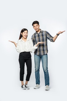 Мужчина и женщина в рубашках и радостно протянули руки в стороны
