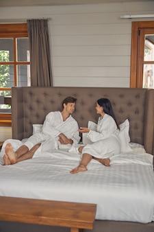 남자와 여자는 침실에서 함께 이야기하는 부드러운 목욕 가운을 입고