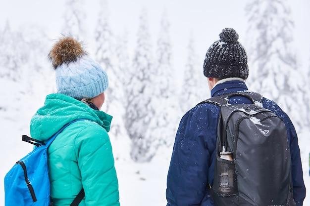 흐릿한 겨울 숲 풍경을 바라보는 배낭을 메고 있는 남녀