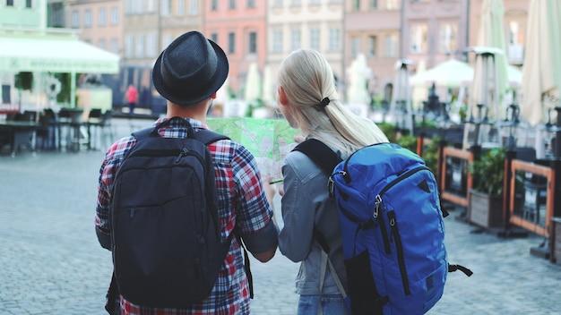 Мужчина и женщина с сумками проверяют карту на центральной площади города