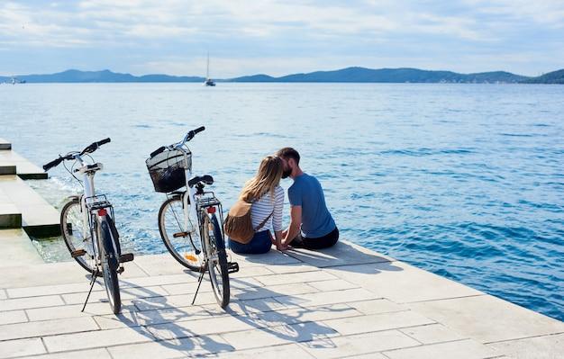 Мужчина и женщина с велосипедами на высоком мощеном каменном тротуаре возле морской воды в солнечный день