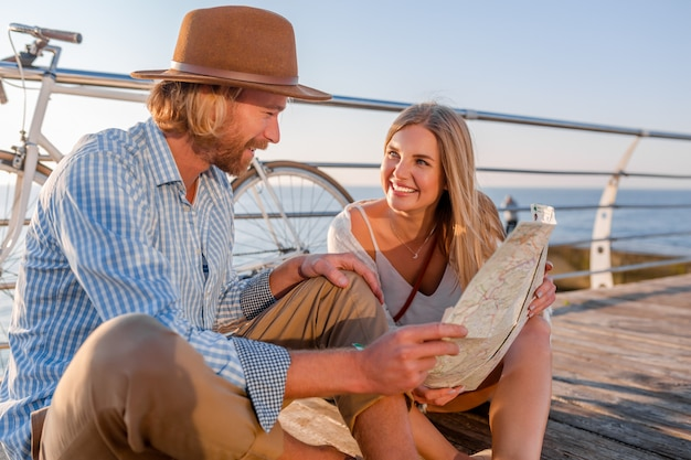 Мужчина и женщина со светлыми волосами в стиле хипстера в стиле бохо веселятся вместе, глядя на карту достопримечательностей