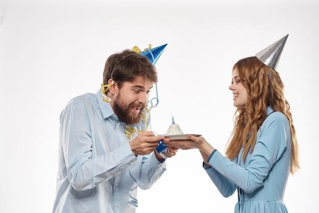 彼らの頭の休日と楽しい誕生日の驚きに帽子をかぶった男と女