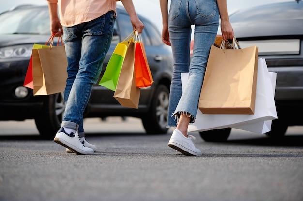 スーパーマーケットの駐車場で段ボールの袋を持つ男女。ショッピングセンター、車両からの購入を運ぶ幸せな顧客