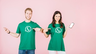 Man and woman with cellphone pointing at their t-shirt with whatsapp icon