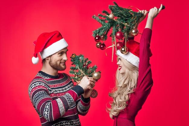 手にクリスマスツリーを持つ男と女おもちゃの装飾クリスマスの楽しみ。高品質の写真
