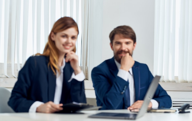 Мужчина и женщина с ноутбуком в офисе, общение, сотрудники, финансы бизнеса