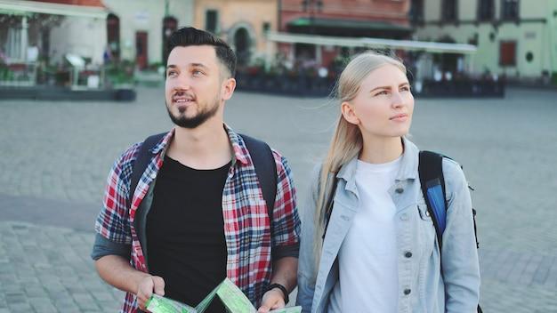 Мужчина и женщина с картой ищут новое историческое место в центре города. они гуляют и находят что-то интересное.