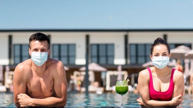 社会的距離を保つマスクを持つ男女